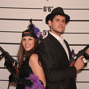 Dallas Murder Mystery party guests pose for mugshots